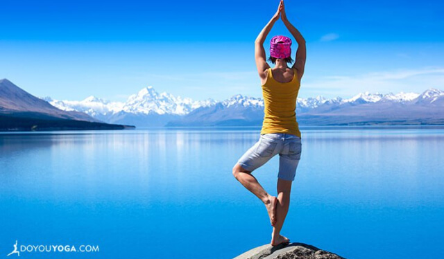 Woman practicing tree pose (vrksasana) in front of beautiful blue lake
