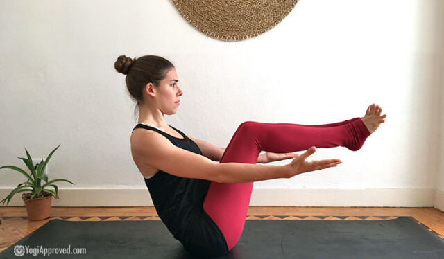 Woman practicing boat pose (navasana) in front of a white wall