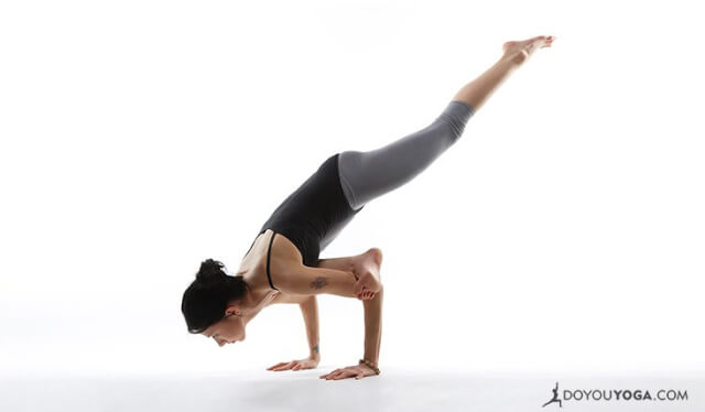 Woman practicing flying pigeon pose (eka pada galavasana) in front of a white background
