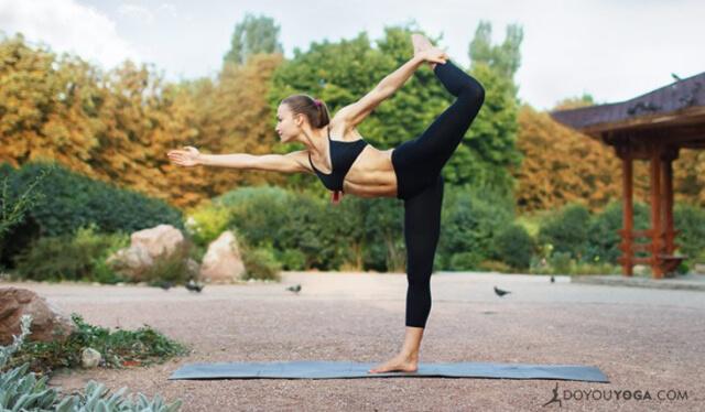 Woman practicing dancer's pose (natarajasana) outdoors