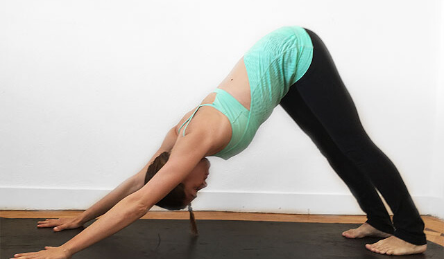 Woman practicing downward facing dog (adho mukha svanasana) in front of white wall