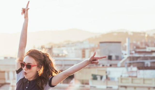 Young woman throwing her arms up in excitement in a new city while traveling