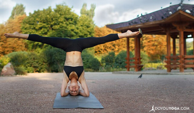 Woman practicing headstand with straddled legs outside