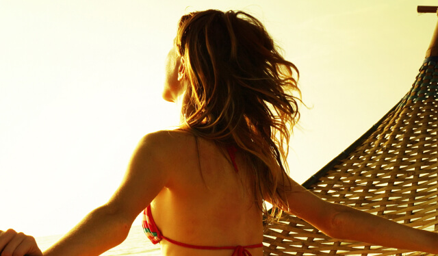 Woman sitting on a hammock at sunset