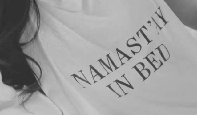 """Close-up of a woman's t-shirt reading """"namast'ay in bed"""""""