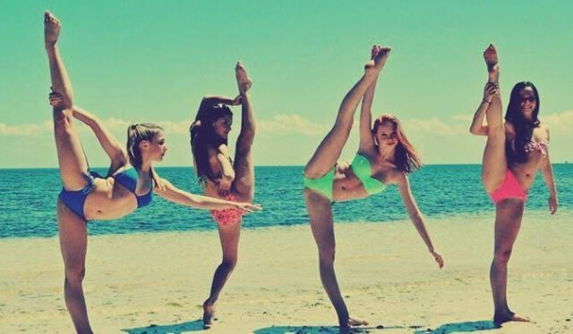 4 women practicing extreme spit stretches on the beach in bikinis