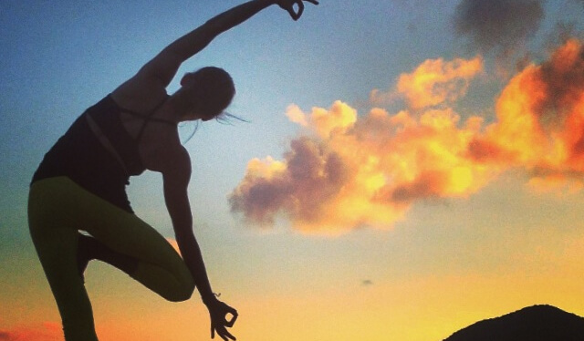 Silhouetted yoga teacher practicing a balancing tree pose (vrksasana) as the sun sets