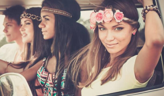 4 smiling young woman sitting in a car with flowers in their hair