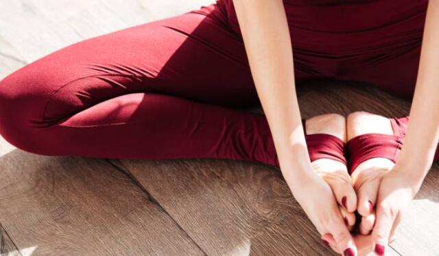Close-up of a woman's legs, sitting in bound angle pose (baddha konasana)