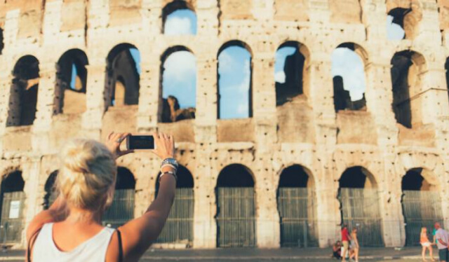 Woman taking a photo of the Colosseum in Rome, Italy