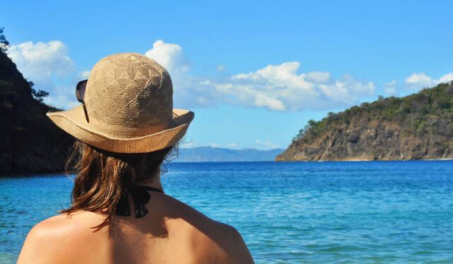 Woman wearing a hat looking out at a beautiful ocean landscape