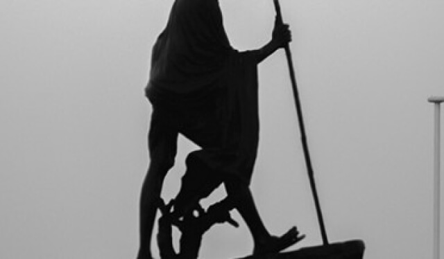 Black and white statue of Gandhi, who preached ahimsa (nonviolence)