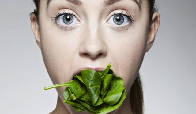 Woman's face with her mouth stuffed full of spinach