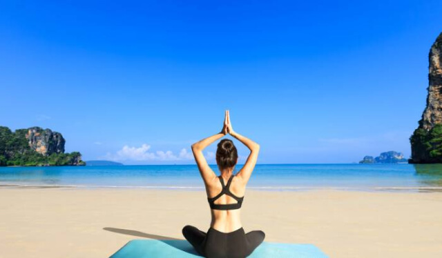 Woman sitting on the beach in meditation