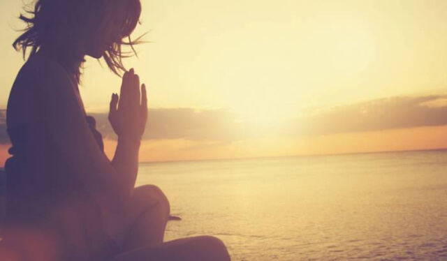 Silhouetted woman sitting in meditation while the sun rises behind her