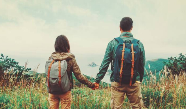 Couple wearing backpacks and holding hands looking out onto a landscape
