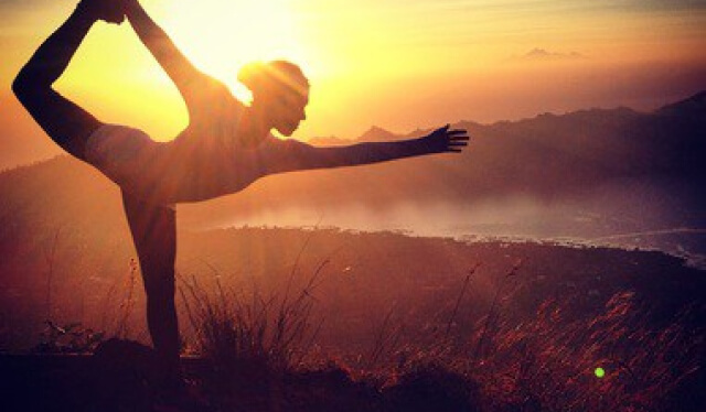 Silhouetted yoga teacher practicing dancer's pose (natarajasana) in front of a sunrise and lake