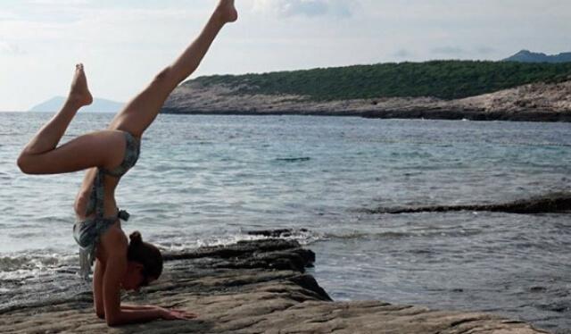 Yoga teacher practicing forearm stand (pincha mayurasana) on a rocky beach