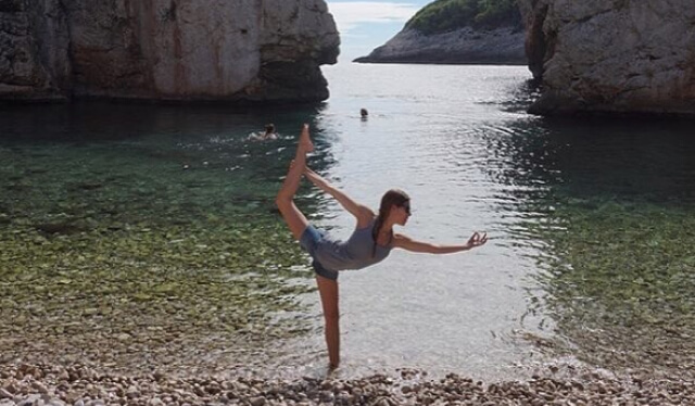 Yoga teacher practicing dancer's pose (natarajasana) while wading in a beautiful beach