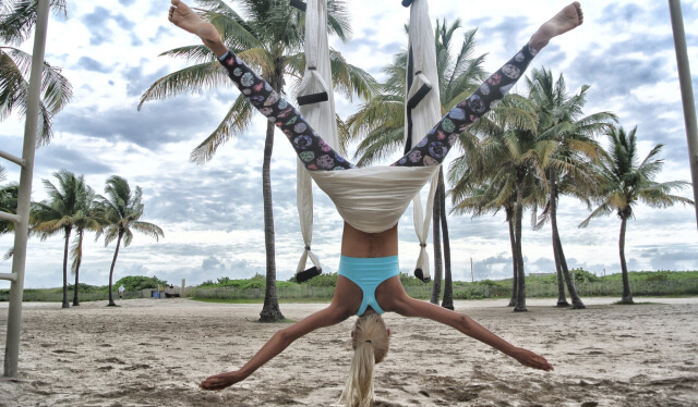 Upside down woman practicing aerial yoga on a beach