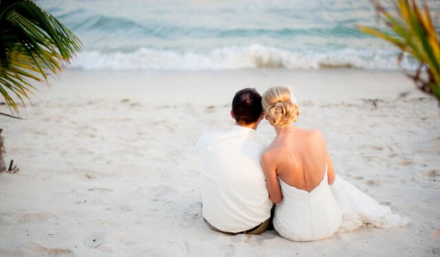 Bride and groom snuggling on a beach