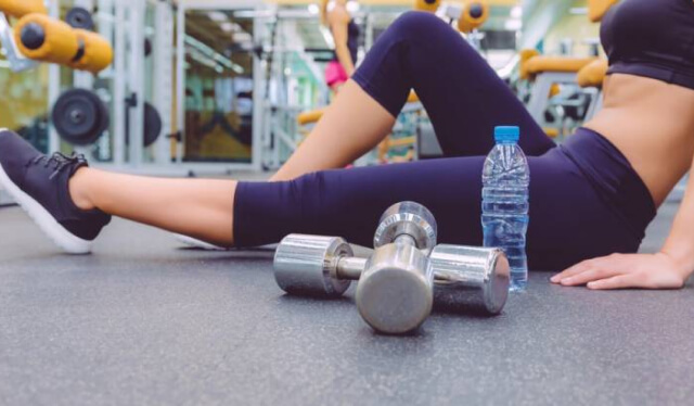 Woman sitting on the floor in a gym with dumbbells and a water bottle next to her