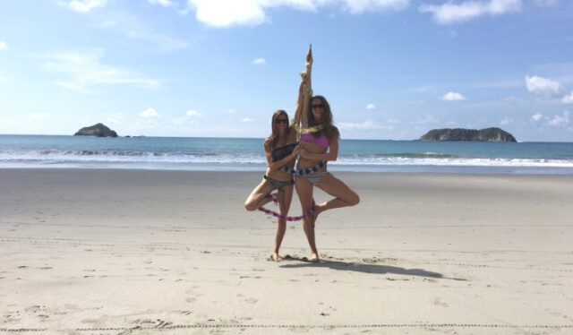 Two women covered in tinsel practicing tree pose (vrksasana) on a tropical beach