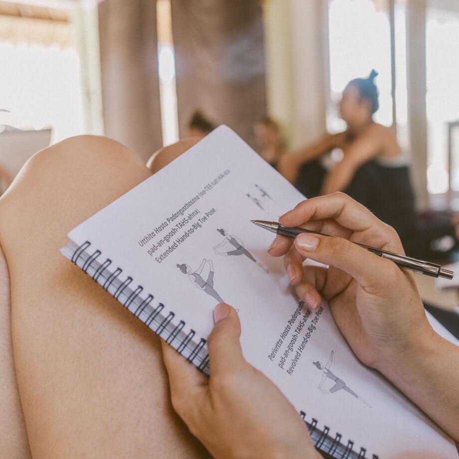 Yoga teacher trainee taking notes in her yoga teacher training manual