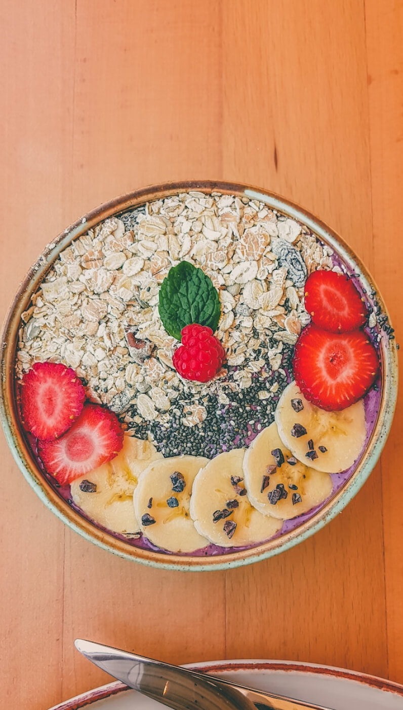 Colorful smoothie bowl filled with fresh fruit on a table