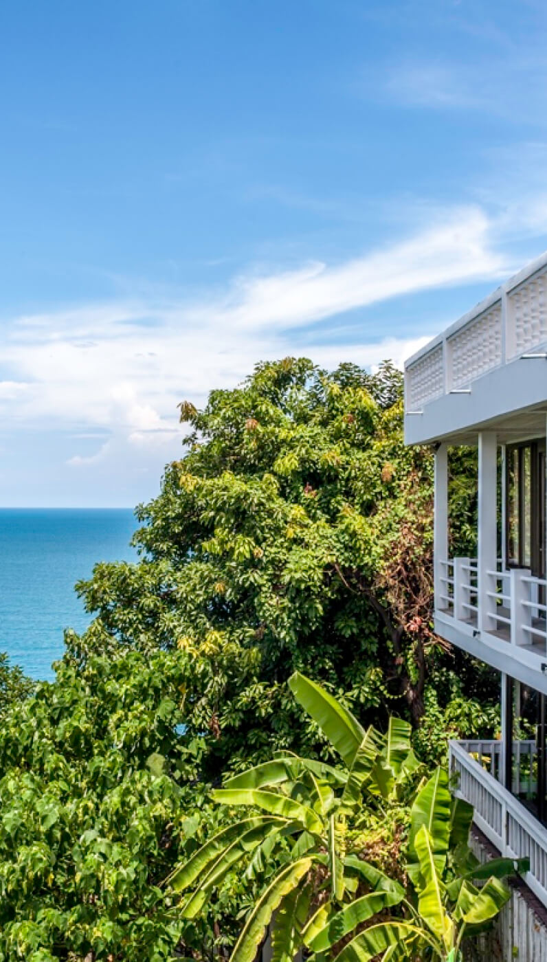 Beautiful ocean panorama view with palm trees and hotel balconies at Vikasa Retreat Center in Koh Samui, Thailand