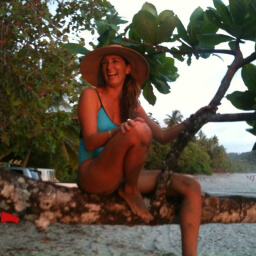 Young woman smiling while perched on tree branch