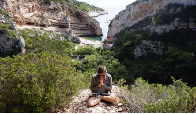 Woman practicing lotus pose overlooking a beautiful sea cove in Croatia