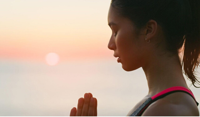 Silhouetted yoga teacher with her hands at her heart in namaste overlooking a sunset on a beach