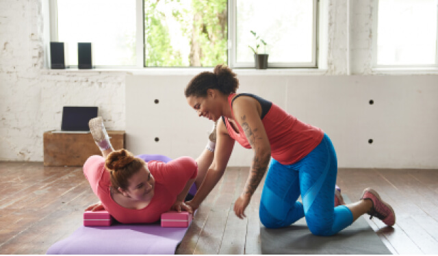 A woman practicing yoga with blocks and another woman (a yoga teacher) instructing her