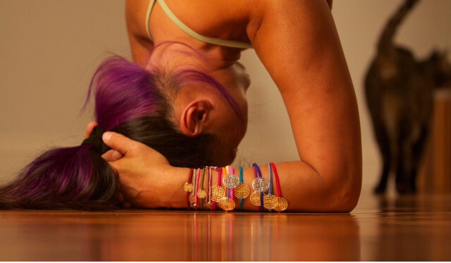 Close-up of a woman practicing headstand (sirsasana) on a wood floor
