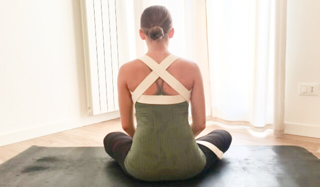 Woman sitting cross-legged with a yoga strap wrapped around her back for shoulder support