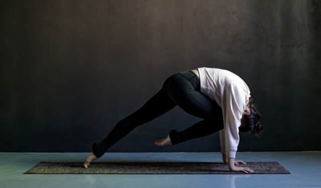 A woman practicing yoga with spinal flexion in a dark room