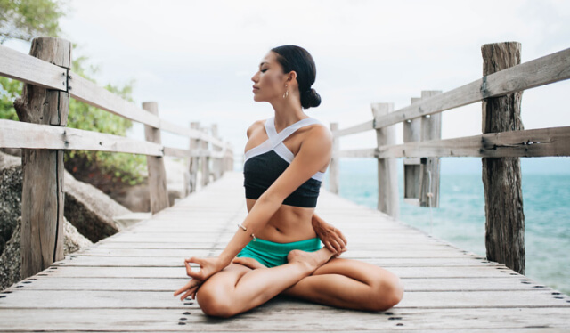 Woman practicing lotus pose with a twist on a boardwalk overlooking the ocean