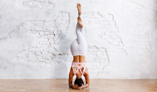 Woman practicing headstand on a wooden floor with a white wall behind her