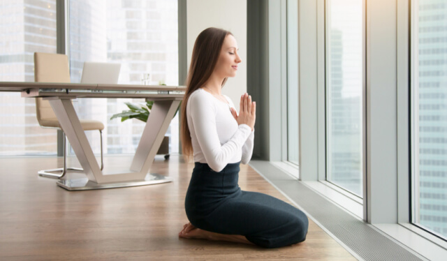Woman kneeling in meditation with her hands at her heart in an office