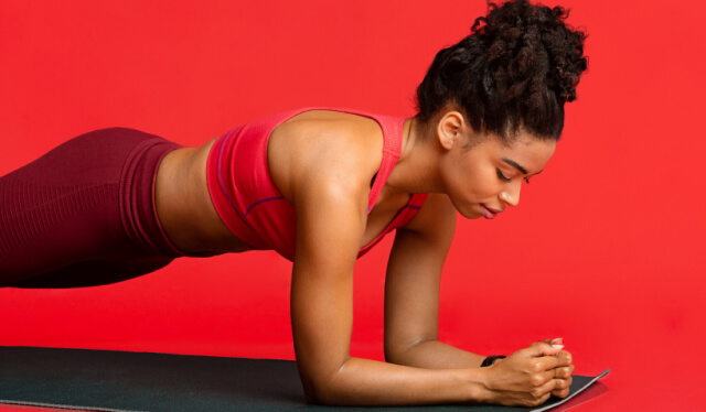 Woman practicing a forearm plank pose on a yoga mat in front of a red wall