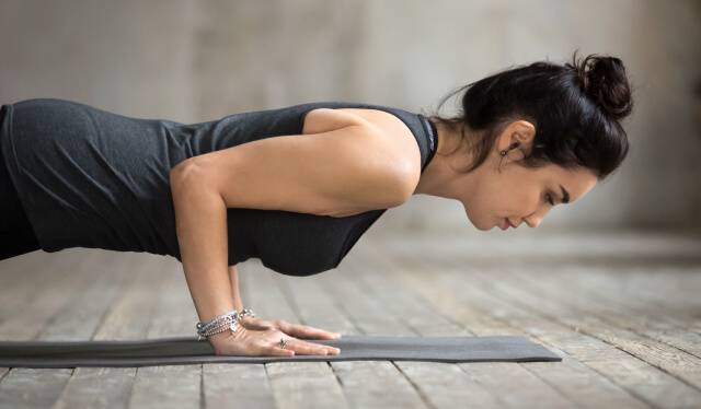 Woman practicing low yogic push-up (chaturanga dandasana) in front of a gray wall