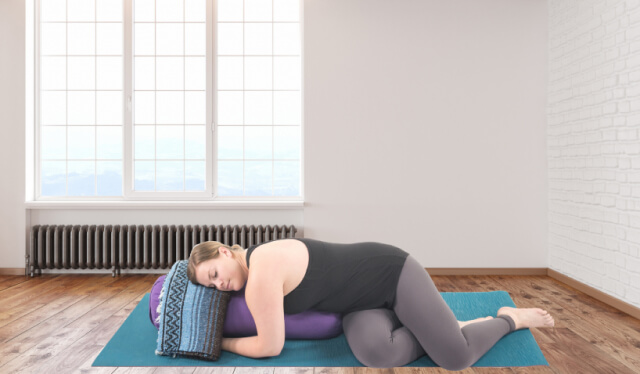 Woman practicing a restorative yoga pose twisted over a blanket and a bolster in a yoga studio