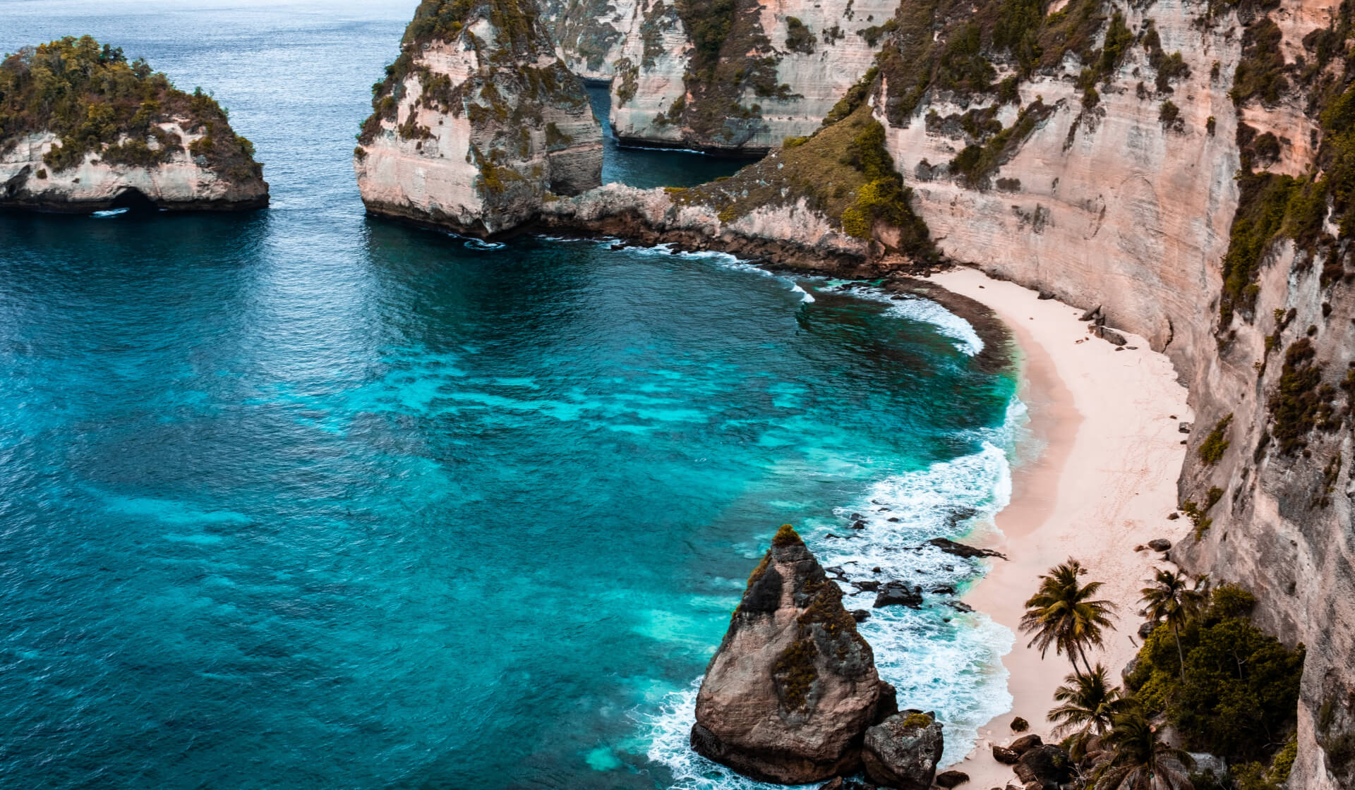 Beautiful, remote, tropical coastline in Bali with crystal clear blue water and a sandy beach below a cliff