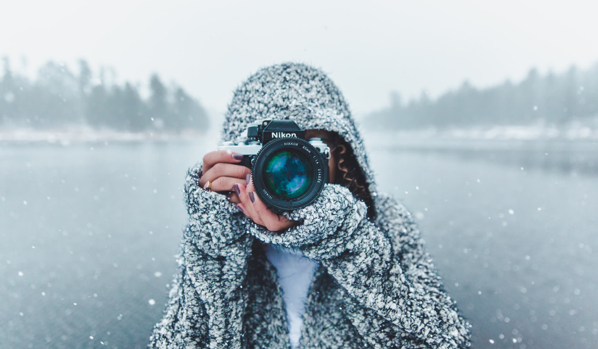 Woman taking a photograph in the snow with hoodie on and a frozen lake behind her