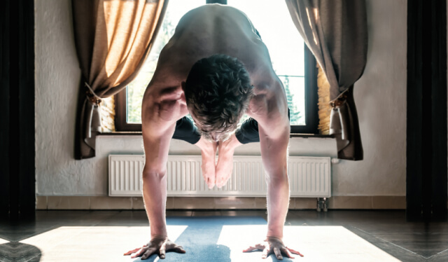 Man practicing the yoga arm balance crow pose (bakasana) in front of a window