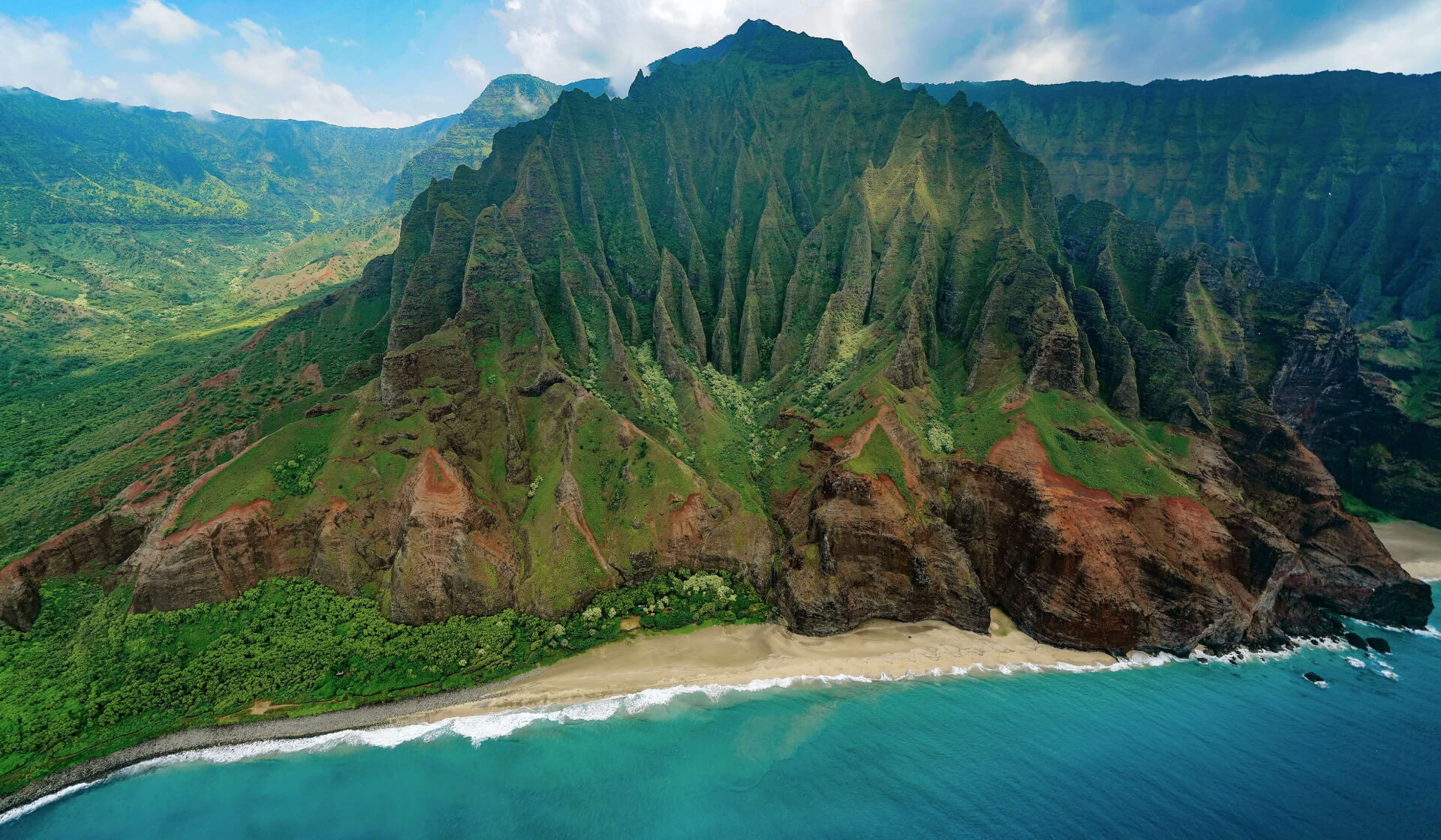 Beautiful green volcanic mountain beside a pristine blue coastline in Hawaii