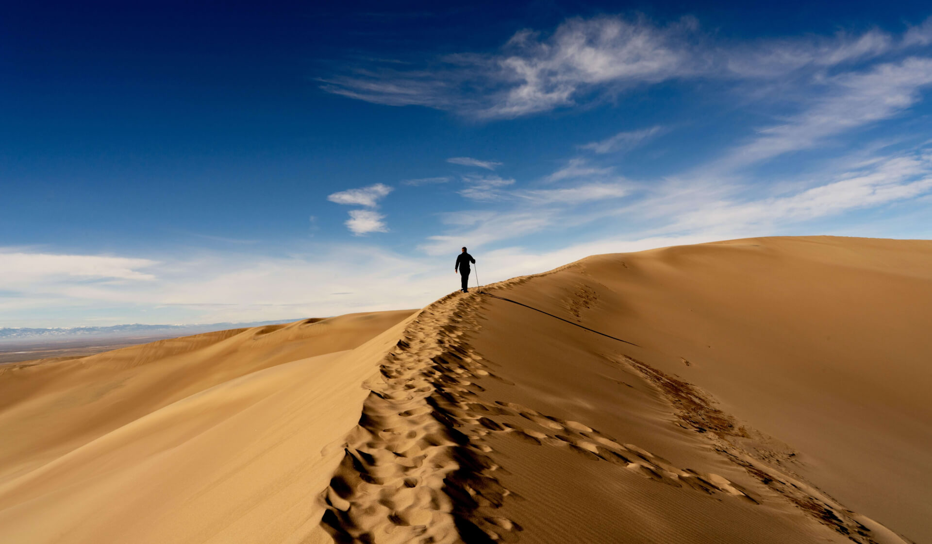 Massive sand dune with footprints and a man hiking across its peak
