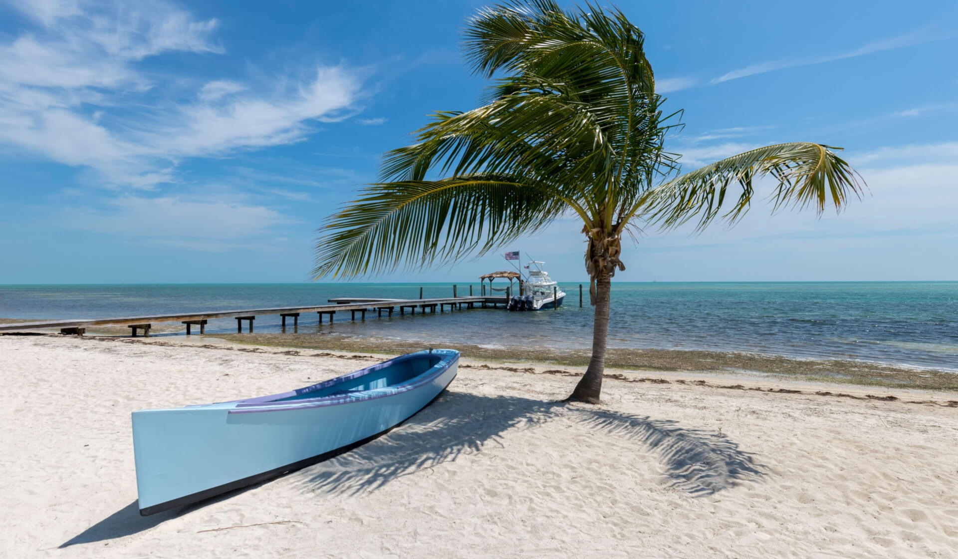 Small blue boat and palm tree on a beautiful tropical beach next to a pier in Florida