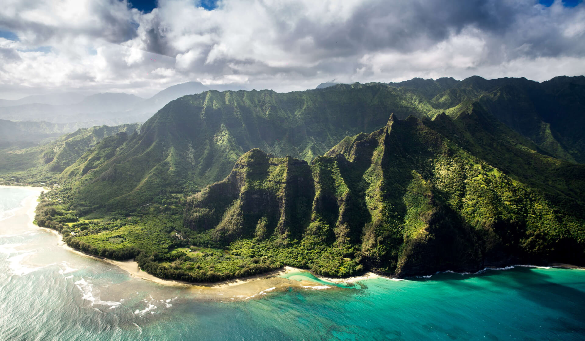 Lush green volcanic mountains along a pristine blue water coast in Hawaii